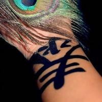 Bold, black, saturated wide hieroglyph hand tattoo