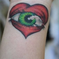 Heart with green eye wrist tattoo