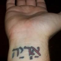 Red ink hebrew wrist tattoo