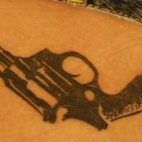 Un gros pistolet réaliste le tatouage sur la hanche à l'encre noir