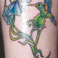Hummingbird with flower tracery coloured tattoo