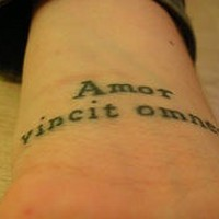 Amor vincit omnia tattoo on wrist
