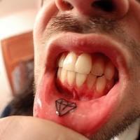 Un petit diamant joli le tatouage sur la lèvre