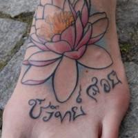 Lotus flower with hindu writings tattoo on foot