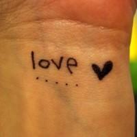 Small love black ink tattoo on wrist