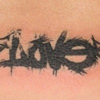 Winged love word tattoo on lower back