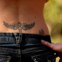 Lower back tattoo, black styled cross with wings