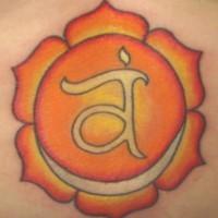 Lower back tattoo, light orange flower, letter in centre