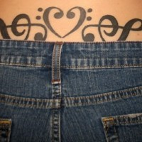 Lower back tattoo, black heart and two treble clefs