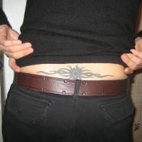 Le tatouage de bas du dos avec un soleil noir en style agitant