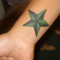 Green and black star tattoo on wrist