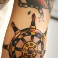 Coloured ship steering wheel tattoo