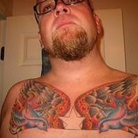 Traditional chest tattoo with star, two doves, fire and wings