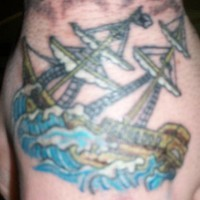 Coloured sailing vessel tattoo on hand