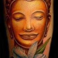 Golden buddha head and flower tattoo