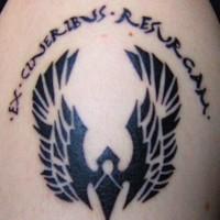 Tatuaggio non colorato sul deltoide il disegno con le ali e la scritta