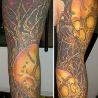 Shoulder tattoo of skulls and trees