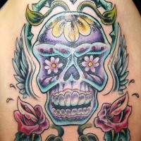 Winged sugar skull with flower tracery tattoo