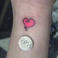 Small pink heart tattoo on wrist