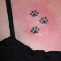 Small paw prints tattoo on chest