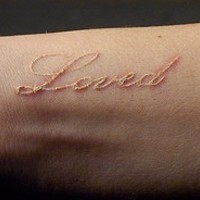 Tattoo in white ink with inscription loved