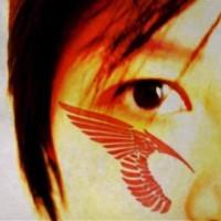 Rotes Tattoo von Engelsflügel auf die Wange