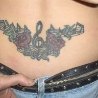 Tattoo on lower back, treble clef, notes, flowers