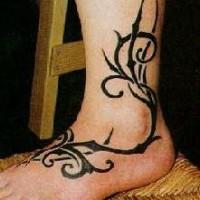Black tribal vine tattoo on foot and leg