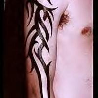 Big tribal arm tattoo of black lines