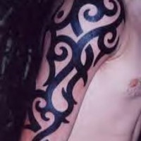 Tribal arm tattoo with thick curved lines