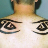 Tattoo of tribal eyes on upper back