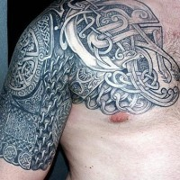 Big tribal tattoo on shoulder and chest