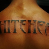 Inscription on upper back white head designed tattoo