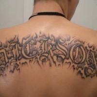 Nickson tattoo black disguised inscription on upper back