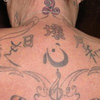 On upper back composition of hieroglyphs tattoo