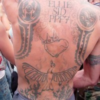 On upper back crowned heart and fireing bird tattoo
