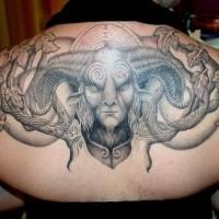 Horned monster in leaves on upper back dreadful tattoo