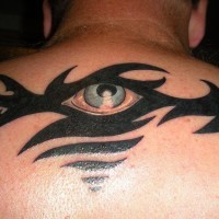 Eye on upper back in black  framing tattoo