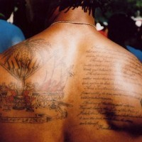 Tatuaggio sulla schiena il testo & la gente attorno della palma