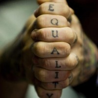 Vertical knuckle tattoo, equality, black styled inscription