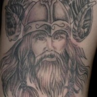 Tattoo of viking warrior in goat horned helmet with braids