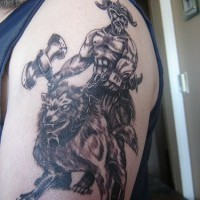 Tattoo of viking warrior with axe on wolf
