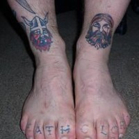 Tattoo of two vikings heads on the legs