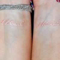 White ink inscription tattoo on wrist