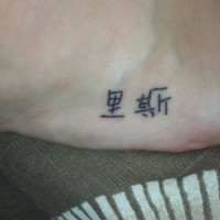 Tattoo am Fuß mit kleinen chinesischen Schriftzeichen