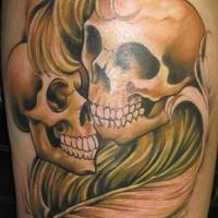 Deux crânes le avec une plume le tatouage