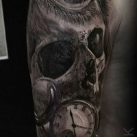 Tatuaggio dettagliato di terrificante braccio superiore del cranio umano con orologio di Eliot Kohek