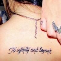 Thin dark black ink lettering tattoo on lady's upper back
