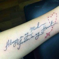 Thin dark black ink memorial lettering with red cross on chain forearm length tattoo