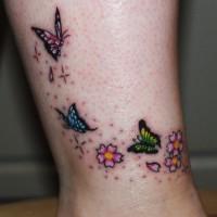 tre diverse piccole farfalle tatuaggio con fiori su gamba